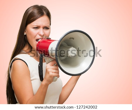 Portrait Of A Young Woman Shouting On Megaphone against a red background