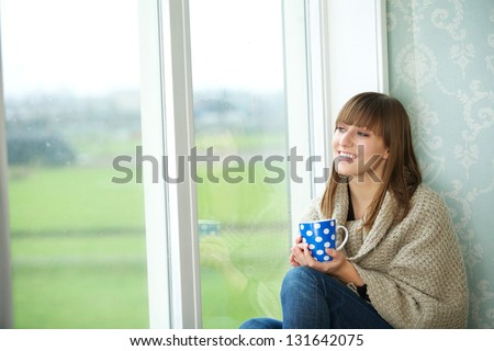Portrait of a young woman sitting by window with cup of tea