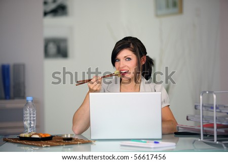 Portrait of a young woman sitting in front of a laptop computer eating a sushi