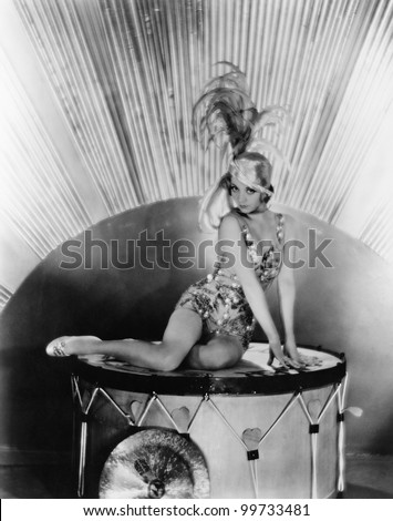 Portrait of a young woman sitting on a drum with a feather hat