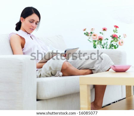 stock photo : Portrait of a young woman sitting on sofa reading book