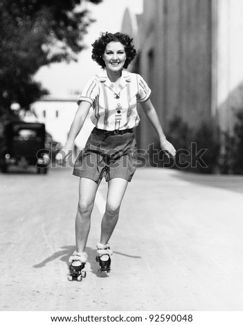 Portrait of a young woman skating on the road and smiling