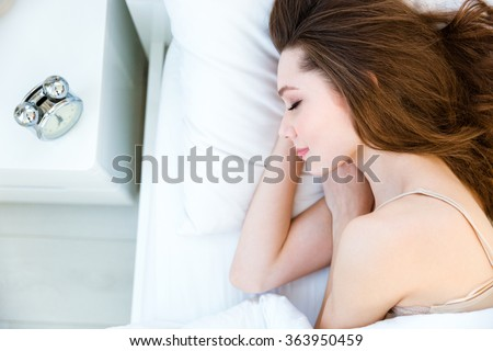 Portrait of a young woman sleeping on the bed at home