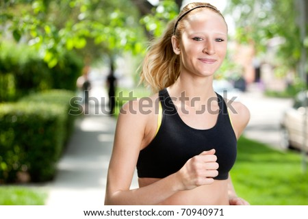 Portrait of a young woman smiling and jogging in the park against blur background