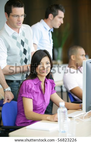 Portrait of a young woman smiling sitting in front of a desktop computer