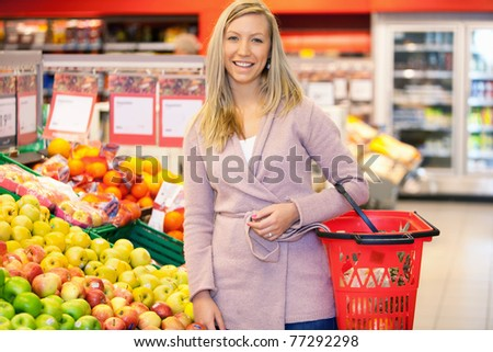 Portrait of a young woman smiling while buying fruits in the supermarket