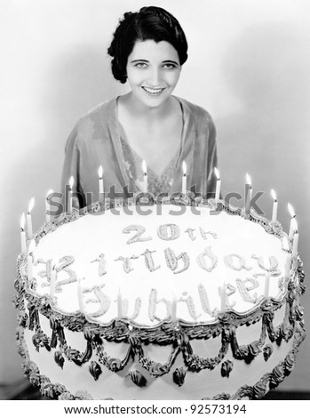 Portrait of a young woman standing in front of a birthday cake