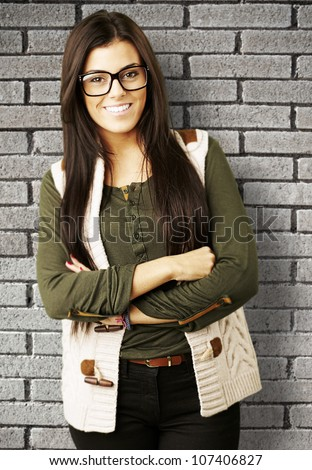 portrait of a young woman standing isolated against a grunge brick wall - stock photo