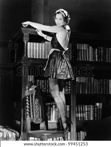 Portrait of a young woman standing on a chair and dusting a bookshelf in a sexy outfit - stock photo