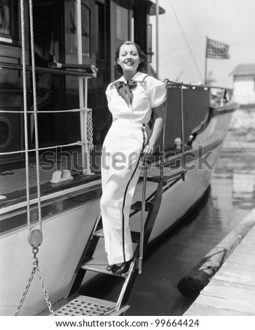 Portrait of a young woman standing on steps of a boat and smiling