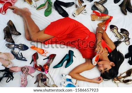 Portrait of a young woman surrounded by shoes on a bed
