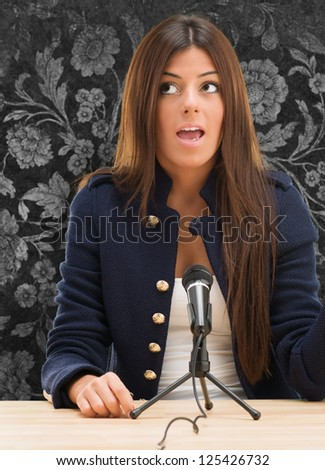 Portrait Of A Young Woman Talking On Mike against a floral pattern background