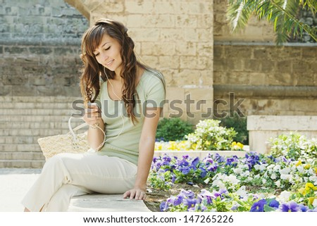 Portrait of a young woman tourist visiting a monument building and using an mp3 player and earphones while sitting down having a break during a sunny day, outdoors.