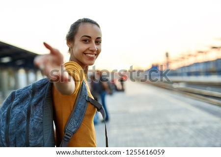 portrait of a young woman traveler with small backpack on the railway stantion. woman waiting for train. Follow me, active and travel lifestyle concept. Сток-фото ©