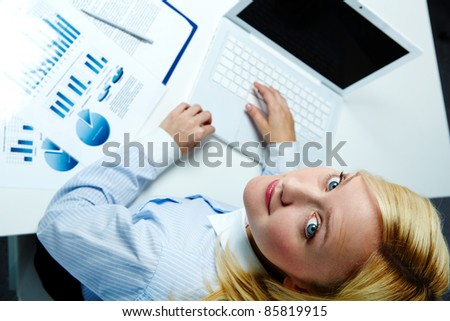 Portrait of a young woman using computer and turning her head to look at the photographer
