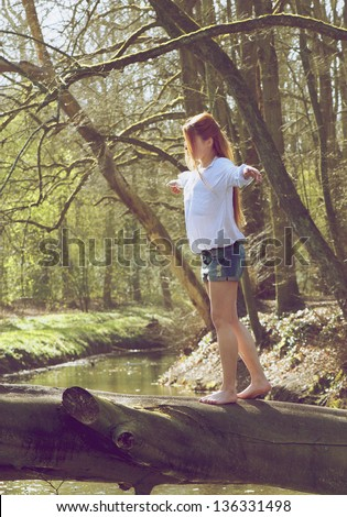 Portrait of a young woman walking over tree trunk showing balance and stability