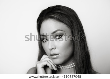 portrait of a young woman wearing a pearl necklace shot on a white background