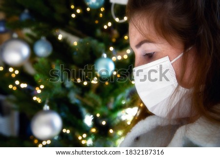 Portrait of a young woman wearing protective face mask and looking sad for Covid-19 with Christmas tree on the background, coronavirus and Christmas concept bokeh