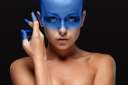 Portrait of a young woman who is posing covered with blue paint in the studio on a black background