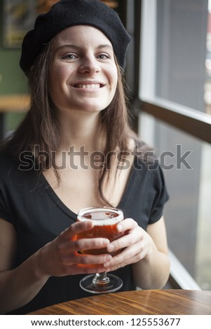Portrait of a young woman with a glass of India Pale Ale