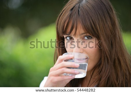 Portrait of a young woman with a glass of water