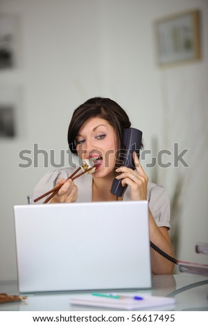 Portrait of a young woman with a laptop computer and a phone eating a sushi