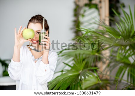 Portrait of a young woman with apple and smoothie drink indoors. Healthy eating and wight loss concept
