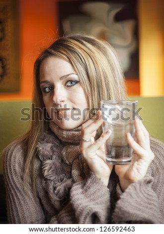 Portrait of a young woman with beautiful blue eyes drinking a glass of ice water. - stock photo