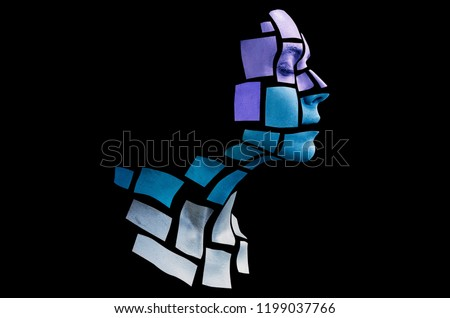 Portrait of a young woman with bold glowing makeup posing in the studio. Shape of cold colored squares on woman face. Isolated on black background.
