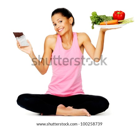 portrait of a young woman with chocolate and vegetables, healthy eating balance scale concept