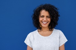 Portrait of a young woman with curly brown hair standing against a colorful blue background and smiling