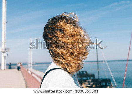 Portrait of a young woman with curly hair on the beach on a windy day