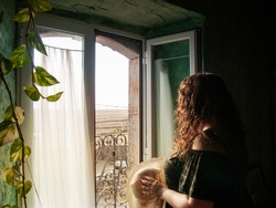 Portrait of a young woman with curly hair wearing a straw hat with natural light coming in and looking through a open window in a rural house