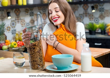 Portrait of a young woman with granola breakfast in the kitchen at home #525064459
