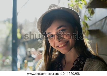Portrait of a young woman with hat; happy woman is smiling and is looking at camera.