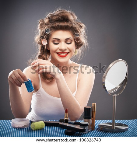 Portrait of a young woman with long hair on gray background isolated.  Happy girl seating at table with make up accessories and mirror. Smiling model with curler hair dress beauty style portrait