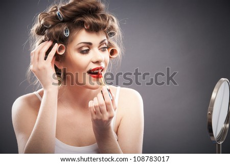 Portrait of a young woman with long hair on gray background making beauty face and hair style. Smile happy girl seating at table with make up accessories and mirror, creating home beauty salon