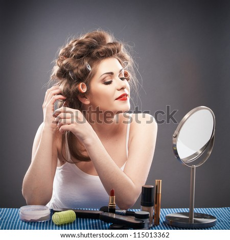 Portrait of a young woman with long hair . Smile happy girl seating at table with make up accessories and mirror