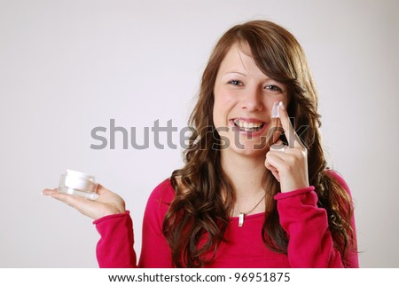 portrait of a young woman with moisturizing cream