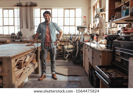 Portrait of a young woodworker smiling confidently while standing next to a workbench full of wood in his carpentry workshop