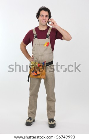 Portrait of a young worker in overalls with mobile phone on white background