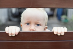 Portrait of abandoned by parents baby boy with staring blue eyes, sad and lonely face expression, looking out through fence. Social problems, family abuse, children stress and negative emotions