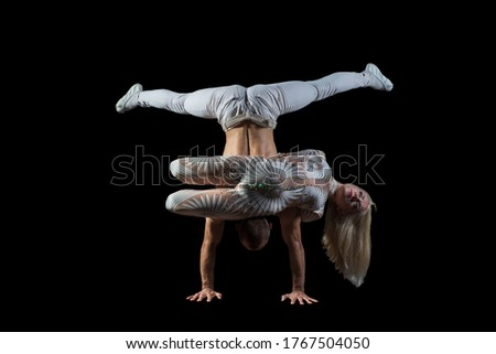 portrait of acrobats guy with a girl in white isolated on a black background. Acrobatic abilities, sport dancing, active lifestyle, perform acrobats stunt on the floor