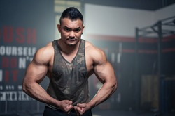 Portrait of Active healthy sport man showing muscles and biceps on arms. Big Bodybuilder guy or athlete showing his physical form, strong male after workout exercising in gym at fitness club or gym.