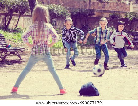Portrait of active junior school girls and boy playing street football #690077179