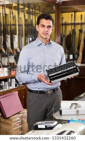 Portrait of active salesman proposing hunting equipments in specialized shop