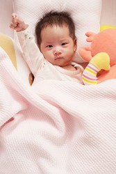 Portrait of adorable Asia baby cute girl wake up on the bed with her doll. Looking at camera