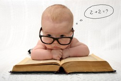 portrait of adorable baby in glasses counting in mind with handwritten thought tag with case study