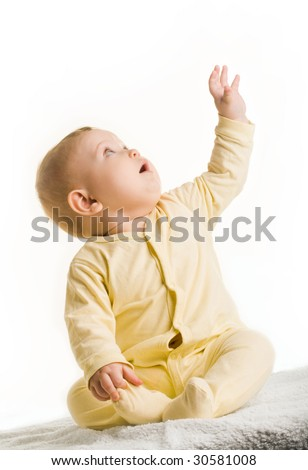 Portrait of adorable baby sitting with his arm raised and looking upwards