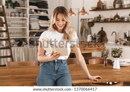 Portrait of adorable blond woman 20s wearing casual t-shirt reading book while standing in stylish wooden kitchen at home